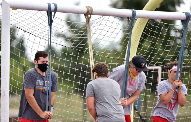 Moon Area High School football players, including senior tight end/defensive end Dalton Dobyns, left, stretch with heavy bands attached to a soccer goal before practice.