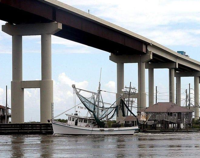 A shrimp boat passes beneath the Leeville Bridge along La. 1 in southern Lafourche Parish.