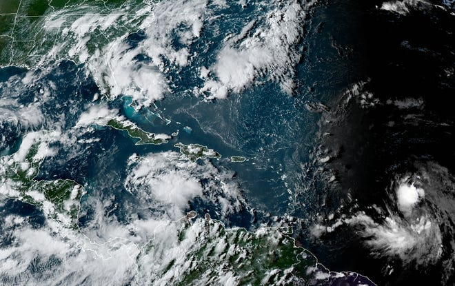 A satellite image shows two storms, one (left, center) near Haiti and the other in the mid-Atlantic (lower right), that forecasters say could threaten the Gulf of Mexico early next week.
