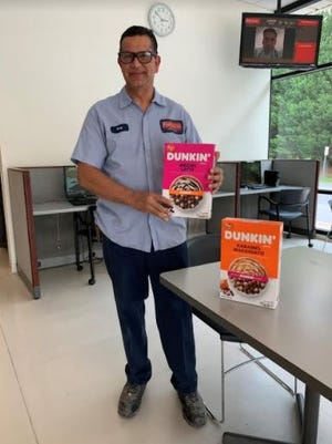 Luis Valerio, Post Consumer Brands Asheboro operations team member, shows off new Dunkin' products.