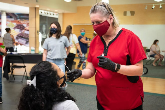 A student gets a Covid-19 swab test at the Lake Square Mall in Leesburg on Wednesday. [Cindy Peterson/Correspondent]