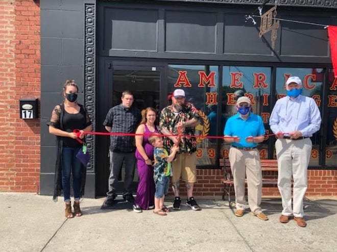 The Lexington Area Chamber of Commerce and Uptown Lexington Inc. participated in a ribbon-cutting ceremony on Aug. 1 for American Heritage Tattoo Co., 17 E. Second St. Pictured standing left to right are Uptown Lexington Director Rebekah McGee, Matt Wingo, Keli Correll, Waylon Corell, owner Chuck Correll, Lexington Mayor Pro-tem Wayne Alley and Lexington Chamber President Joe Wallace.