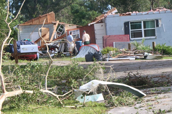Residents survey damage along Washington Street in DeLand on Wednesday, the day after an EF-2 tornado hit the city.