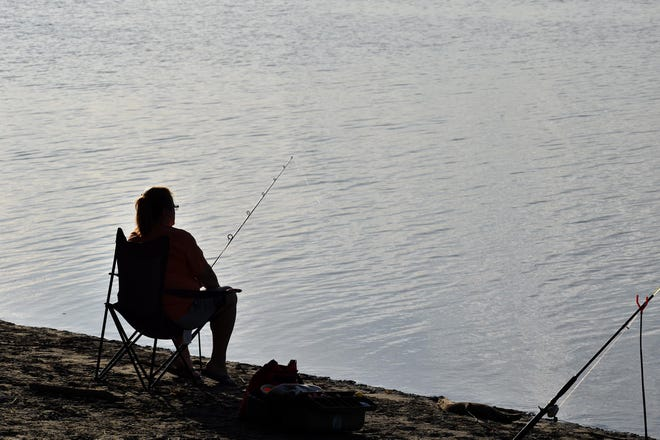 A person fishing on the Mississippi River is shown at Tama Beach River Access in Burlington.