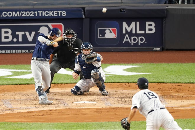 Tampa Bay Rays Brandon Lowe follows through on a three-run, home run off New York Yankees starting pitcher Masahiro Tanaka (19) during the third inning of a game Tuesday in New York. Yankees catcher Gary Sanchez is behind the plate as home plate umpire Chad Fairchild watches.