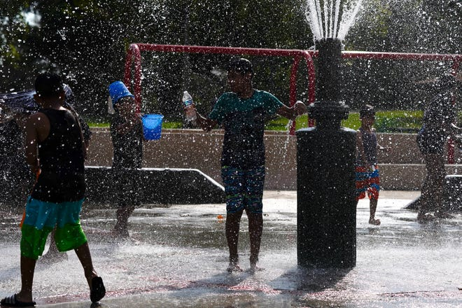 Children cool off in a park Tuesday in Fountain Valley, Calif. The state is in a days-long heat wave that has stressed the electrical system and resulted in rolling blackouts over two nights last weekend. (AP Photo/Jae C. Hong)