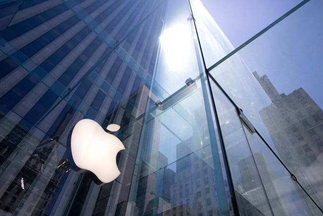 In this June 16, 2020, file photo, the sun is reflected on Apple's Fifth Avenue store in New York. Apple is the first U.S. company to boast a market value of $2 trillion, just two years after it became the first to reach $1 trillion. Apple shares have gained nearly 60% this year as the company overcame the shutdown of factories in China that produce the iPhone and the closure of its retail sales amid the coronavirus pandemic.  (AP Photo/Mark Lennihan, File)