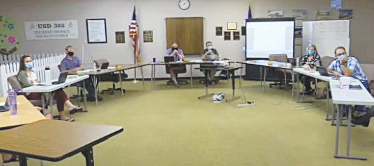 Members of the USD 382 Board of Education listen to a parent speak during their August 10 meeting. Students in certain classes and age groups will be required to wear masks when they go back to school on August 26.
