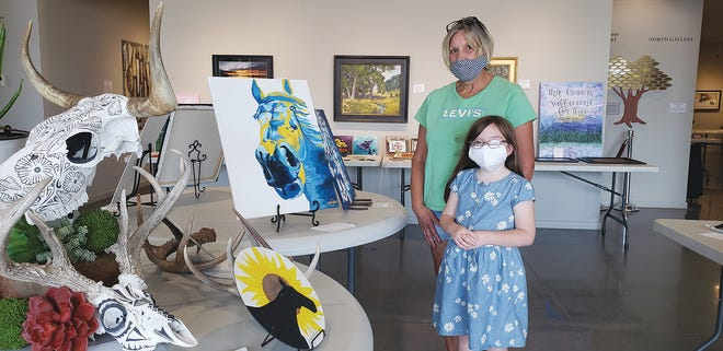 Vernon Filley Art Museum Board Member Cindy Tilley and eight-year-old Aliyah Tilley check out artwork by Sophie Bricker, part of the Community Art Show now on display. The exhibit includes 125 works of 47 area artists.