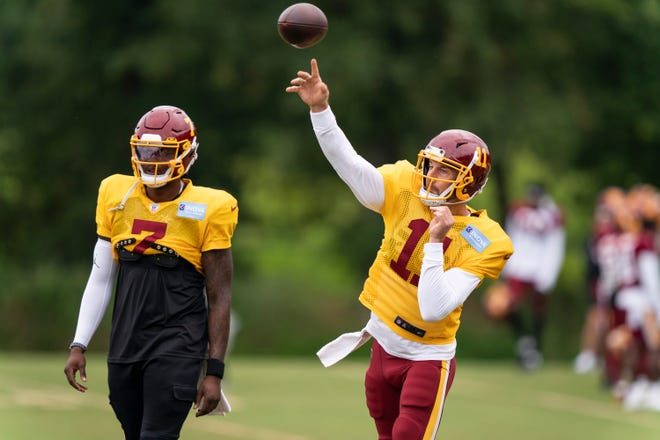 Washington quarterback Alex Smith, right, throws with quarterback Dwayne Haskins Jr. watching during Wednesday's practice in Ashburn, Va. [AP Photo/Alex Brandon]