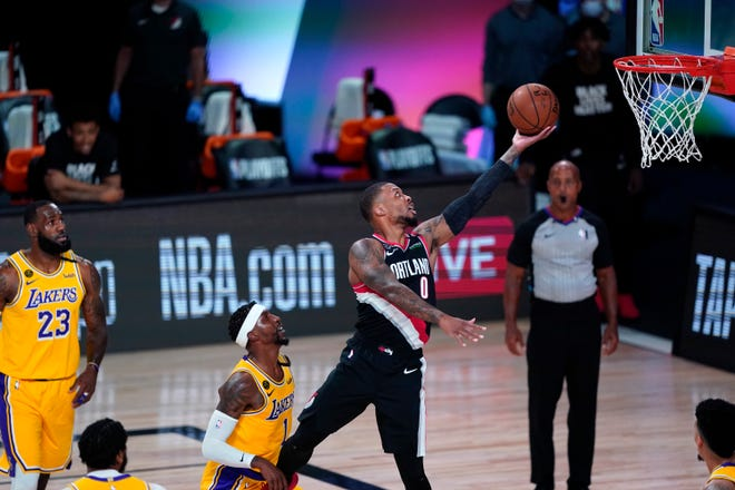Portland's Damian Lillard beats Los Angeles Lakers guard Kentavious Caldwell-Pope to the basket during the first half of the Trail Blazers' 100-93 win over the Lakers in Tuesday's first-round playoff game in Lake Buena Vista, Fla. [AP Photo/Ashley Landis]