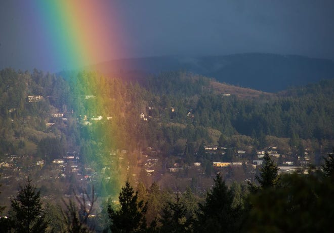 A rainbow touches down in the south hills of Eugene during a sun break on a rainy afternoon.