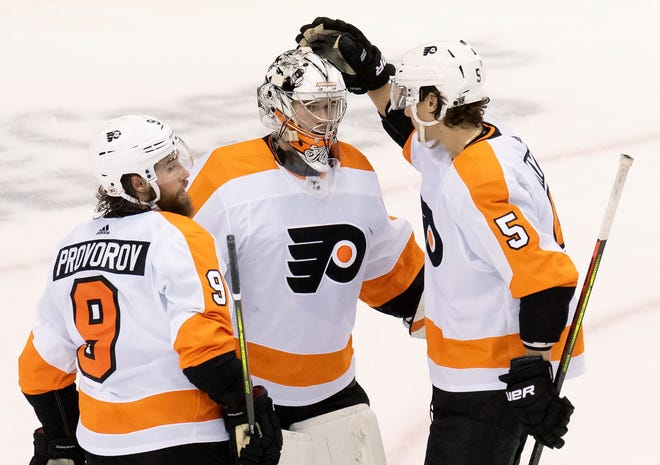 Philadelphia Flyers goaltender Carter Hart, center,  is congratulated on his shutout performance by defensemen Ivan Provorov (9) and Philippe Myers following Tuesday's 2-0 playoff win over the Montreal Canadiens. [Frank Gunn/The Canadian Press via AP]