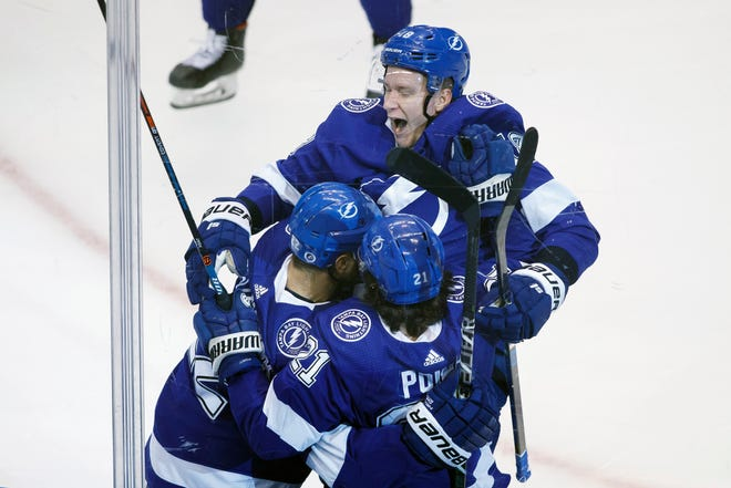 Tampa Bay Lightning center Brayden Point (21) is embraced by teammates to celebrate his game-winning goal during overtime of an Eastern Conference Stanley Cup first round playoff game against the Columbus Blue Jackets in Toronto, Wednesday, Aug. 19, 2020. COLE BURSTON / THE CANADIAN PRESS VIA AP