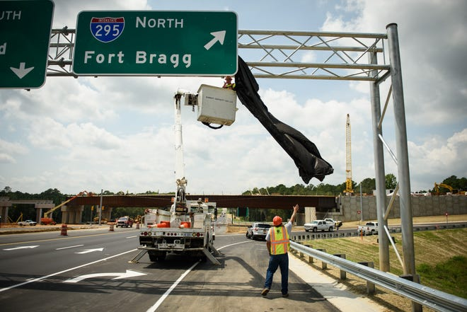 Workers remove the covering on the Interstate 295 on ramp sign on Raeford Road as they prepare to open a 2.7-mile segment of the Fayetteville Outer Loop on Wednesday. The section runs from Cliffdale to Raeford roads.