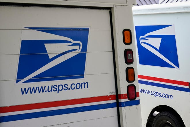 Mail delivery vehicles are parked outside a post office. [AP Photo/Nati Harnik, File]