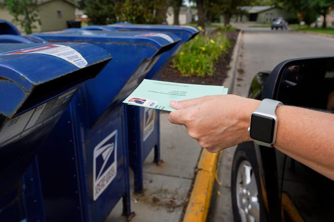 A person drops applications for mail-in ballots into a mail box. [AP Photo/Nati Harnik]