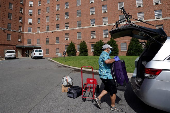 A parent packs a student's belongings Tuesday at a University of North Carolina dormitory following a cluster of COVID-19 cases on campus that caused the university to cancel all in-person undergraduate classes. [AP Photo/Gerry Broome]