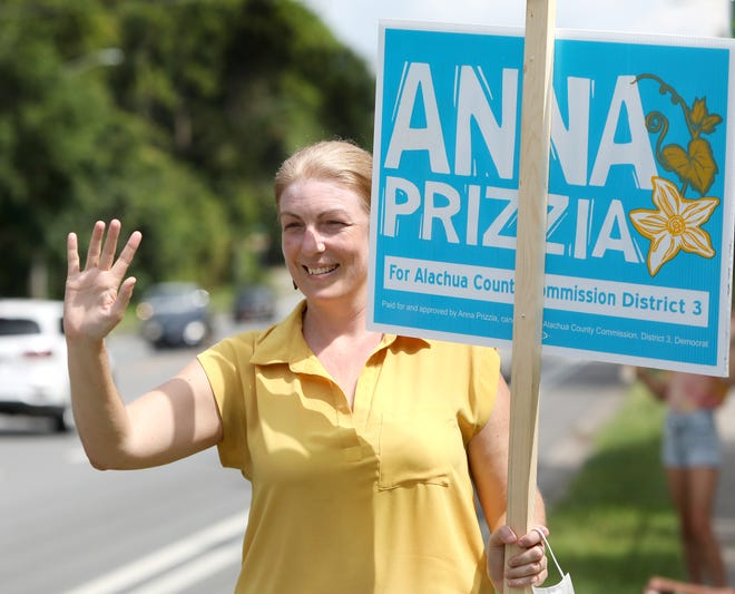 Anna Prizzia, a candidate for the Alachua County Commission District 3 seat, waves to motorists as she campaigns on Election Day outside the Millhopper Library in Gainesville Fla. Aug. 18, 2020.