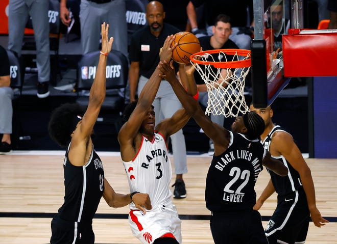 Toronto's OG Anunoby draws a foul against Brooklyn' Caris LeVert as Jarrett Allen defends.
