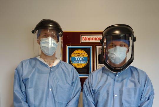 Eric Adler (left) and Michael Adler (right) don their PPE at Adler Family Dental in Aberdeen