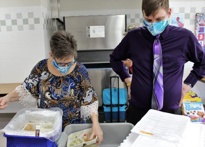 Clairissa Tucker places meal trays in an insulated bag under the watchful eye of her son, Joel. They also prepare bags with drinks and dessert for each recipient.