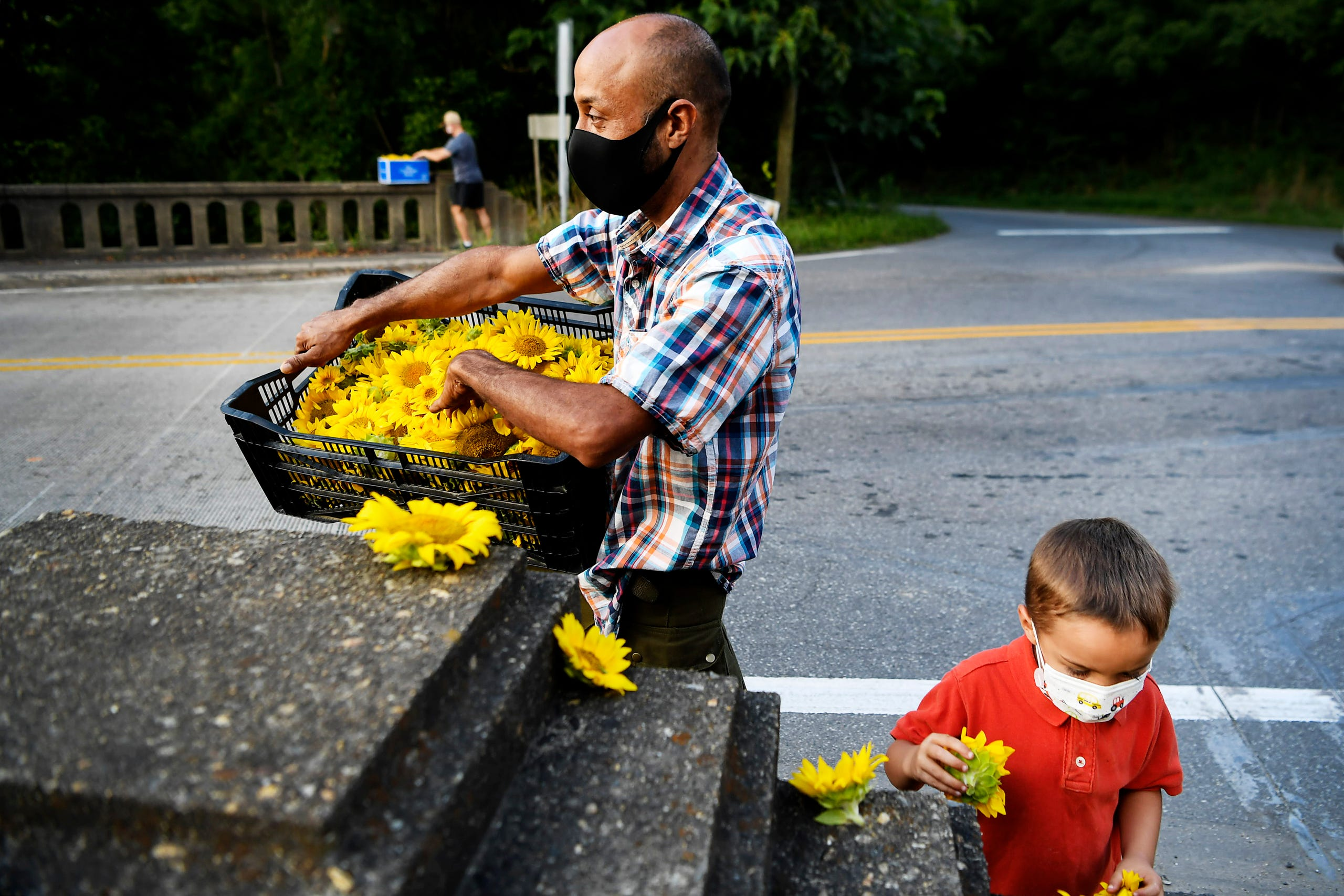 Hans Banzer and his son, Charlie, place flowers along the Craggy Bridge in Woodfin August 19, 2020.