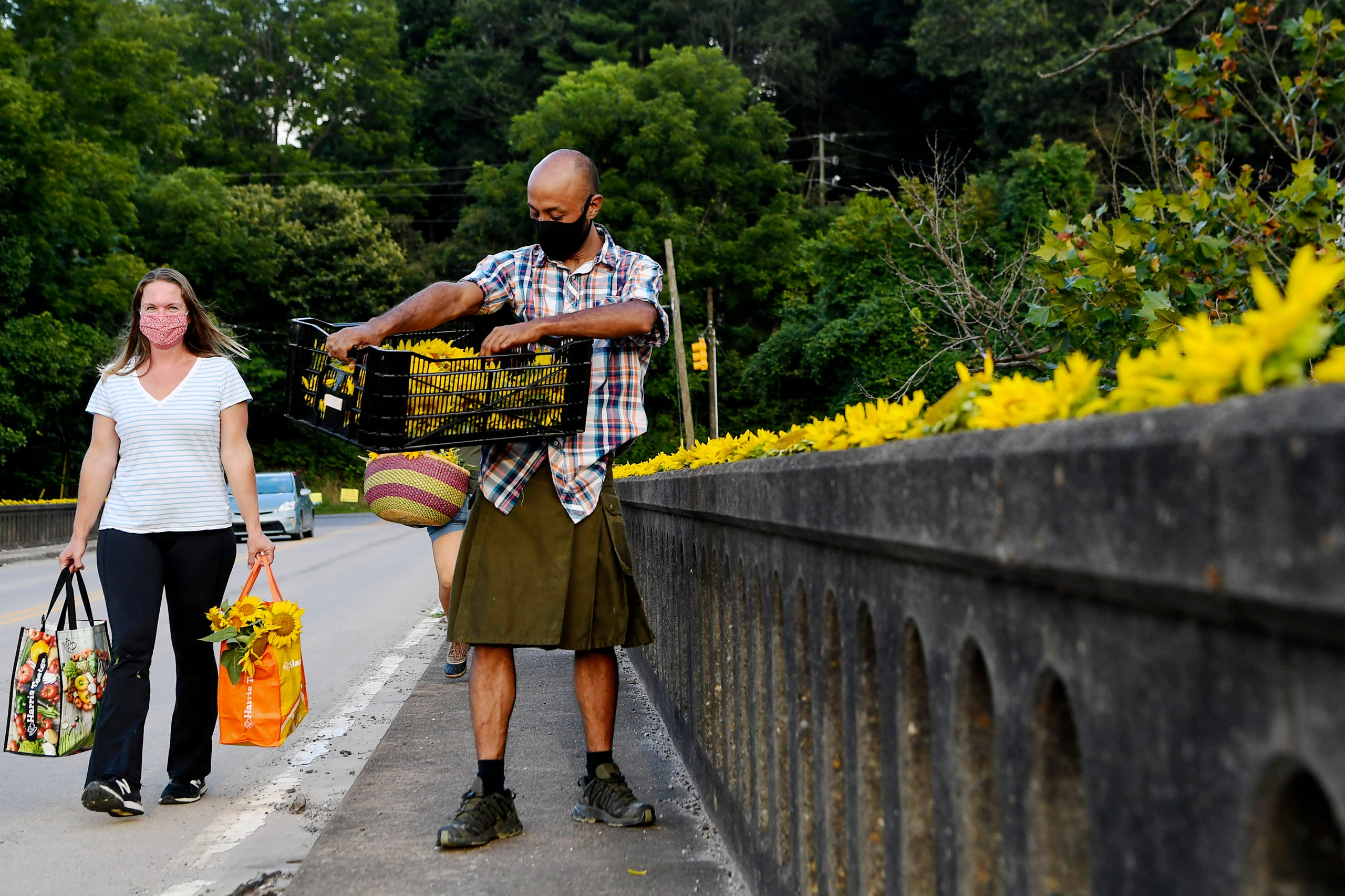 Hans Banzer lines Craggy Bridge with sunflowers in Woodfin as Sarah Pica carries more flowers to the scene August 19, 2020.