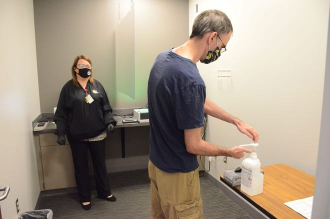 Doug Main of Battle Creek uses hand sanitizer before he is fingerprinted Wednesday by Jeniffer Fisher at the Calhoun County Sheriff Department.  Trace Christenson/The Enquirer