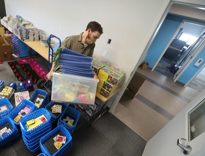 With classroom supplies in hand, first-grade teacher John Bachner carefully makes his way through the student supply baskets being assembled on the floor and heads for his classroom at Catalyst Public Schools in Bremerton on Wednesday Aug. 19, 2020.