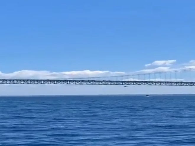 A screenshot of video taken by a crew of the U.S. Coast Guards shows a plane under the Mackinac Bridge in June 2020.