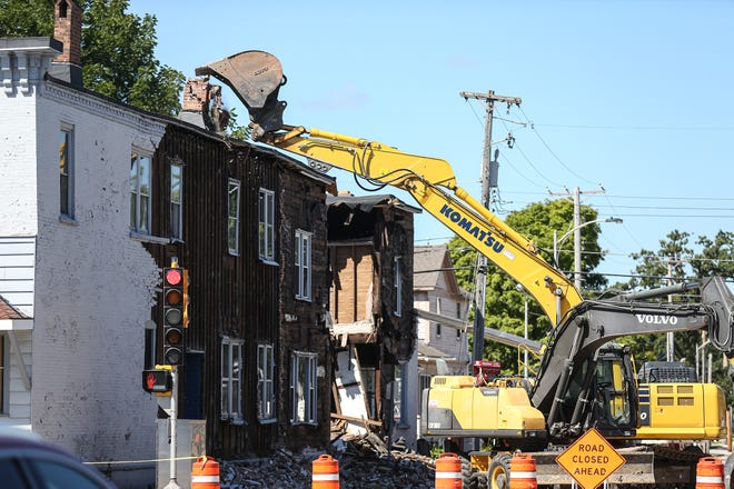 A man in a track excavator topples a chimney on a building getting razed Tuesday at 350 S. Main St. in Fond du Lac.