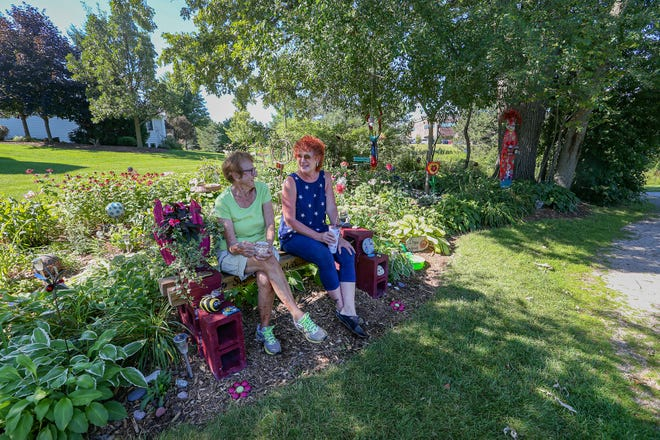 Delores Brookins and Karen Jo Dobyns sit and talk  in a garden they created over the last couple years on city property near their houses along the walking/bike path off of Knights Way.