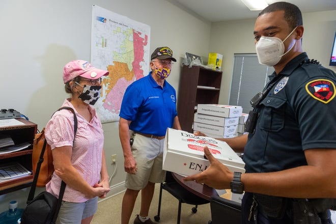 Officer Logan Signator receiving lunch from  Neighborhood watch organizers Myron Fonseca and Stacie Devereax showing their appreciation for first responders by providing meals for officers. Wednesday, Aug. 19, 2020.