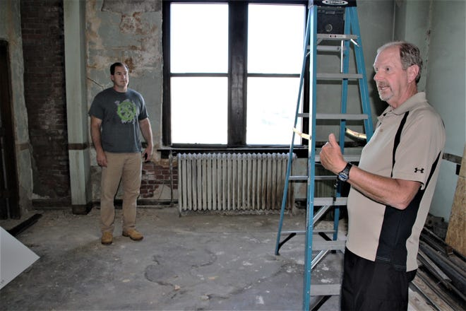 Regan J. Hensel, right, Leapin' Outreach Center board chairman, describes plans for 11 rooms that will house women at the homeless shelter being built on the second floor of the facility at 150 Court St. in downtown Marion. Rev. Joe Couch of Marion Grace Church listens as Hensel talks about the plans for the facility.