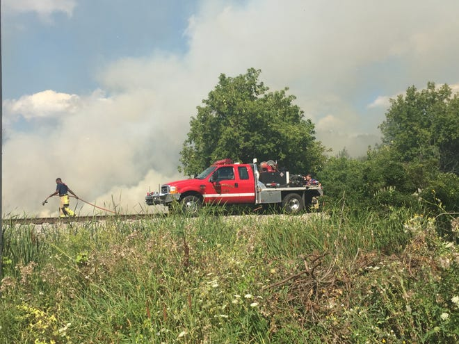 A Mequon firefighter stretches a hose line and prepares to fight a brush fire in Germantown on Tuesday afternoon.