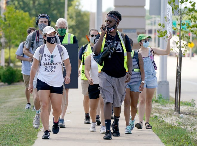 Will Toney, center, of Glendale, leads a chant as the Break the Silence in the Burbs group marches on Wednesday, Aug. 19, 2020.
