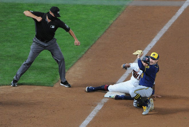 The Brewers' Brock Holt gets the Twins' Ildemaro Vargas out at third base in the 11th inning Tuesday night after scooping up a throw from Jedd Gyrko.
