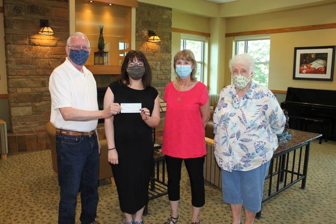Nealus Wheeler, President of the Friends of the Library, presents a scholarship to Baxter County Library staff member Laura Clark, along with Scholarship Committee members JoBelle Zimmerman and Nancy Knopp.