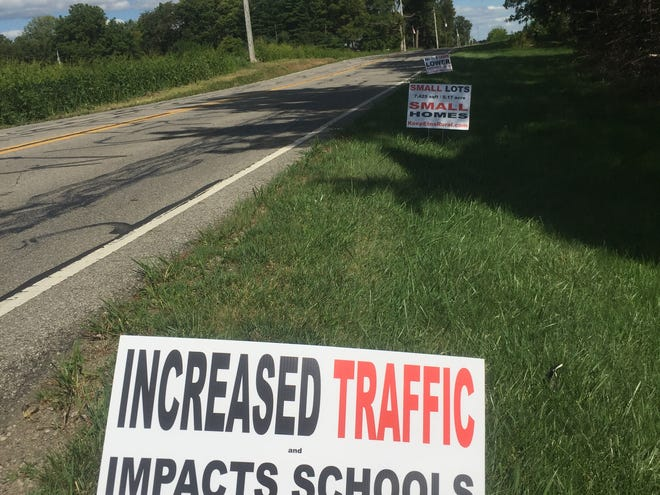 Signs posted along Palmer Road near the entrance to New England Acres argue against a proposed rezoning for a housing development opposed by neighbors and the Southwest Licking School District.