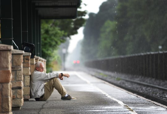 A man sits on a platform at Radburn train station as he waits for a train to come as rain falls in Fair Lawn on 08/19/20.