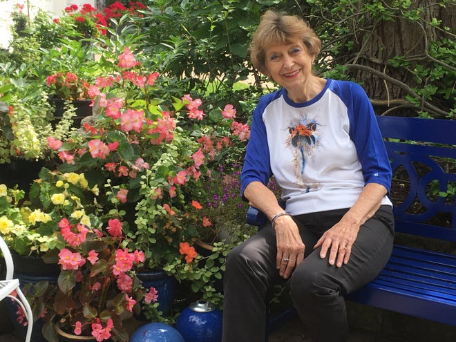 Julie Dawson sits in the courtyard garden surrounded by begonia plants in royal blue ceramic pots. She enjoys dining in this area close to the bells on display.