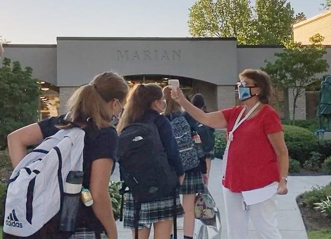 Sister Lenore Pochelski, IHM, head of Marian High School, checks temperatures of students returning for the new 2020-21 school year.