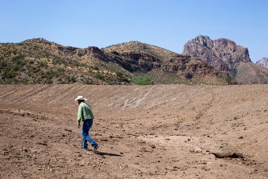 Jeremy Cluff walks across a dry stock tank, August 19, 2020, at the Battle Axe Ranch, south of Superior, Arizona.