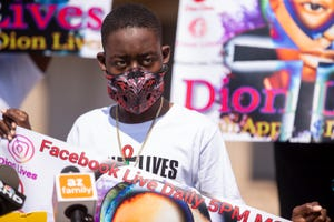 19-year-old Dion Humphrey listens as his father, William Humphrey, speaks about a use-of-force incident against Dion and the time it took for the report to be released, during a press conference on Aug. 19, 2020, outside Phoenix Police Department headquarters.