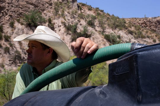 Jeremy Cluff fills a 300-gallon tank so he can haul water to his cattle on Aug. 19, 2020, at Battle Axe Ranch, south of Superior, Arizona.