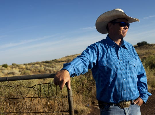 Trenton Hancock, a cattle rancher, stands at the gate to one of his grazing fields near St. Johns, Arizona. He has been hauling water for his cows and feeding them hay during the drought.