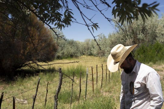 Cattle rancher Kevin McFee stands in front of land he has been forced to lease to feed his cows in St. Johns, Ariz. on Aug 13, 2020. He said leasing the pasture, which has more grass for cattle than other nearby lands, is one step he's taking
