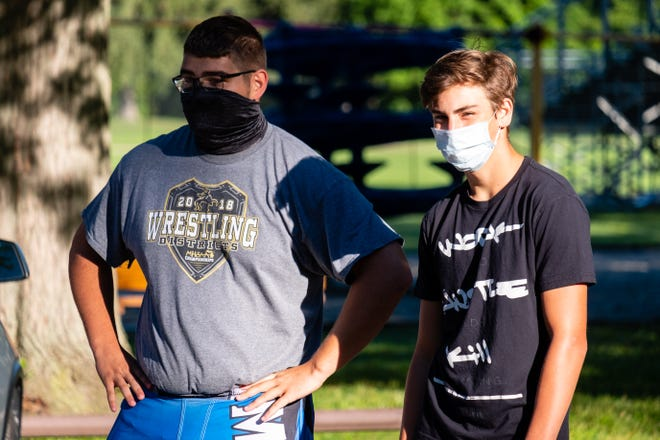 Former Yale football players Aaron Johnson, left, and Marty Siwack listen to direction during a cross country practice Wednesday, Aug. 19, 2020, at Yale Park. After the MHSAA announced last week they were moving football to the spring, several members of Yale's football team joined the cross country team.
