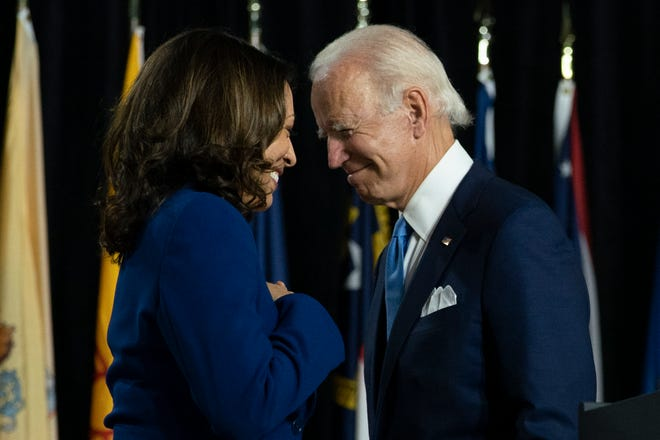 Democratic presidential candidate Joe Biden and his running mate, Sen. Kamala Harris, D-Calif., pass each other as Harris moves to the podium during a campaign event at A.I. du Pont High School in Greenville on Aug. 12, 2020.